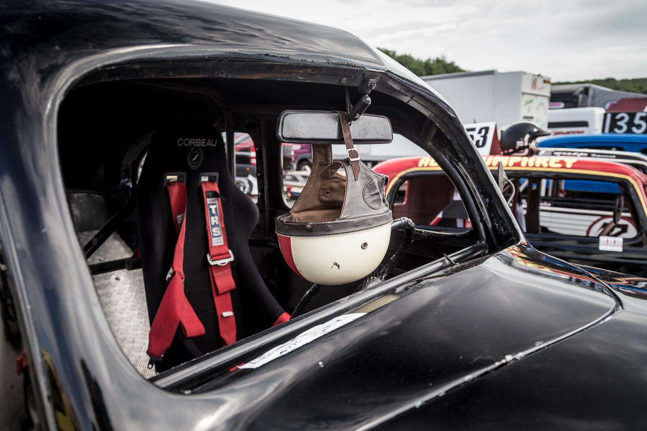 Race crash helmet hanging from car mirror