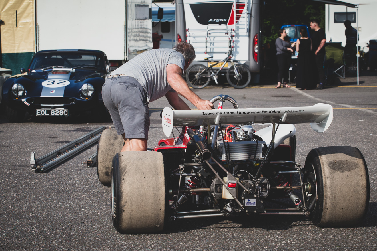Pushing historic formula 1 car through the paddock